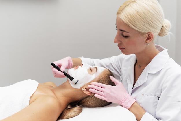 Profesjonalna kosmetyczka nakłada biały krem kosmetyczny na dziewczynę leżącą na kanapie w nowoczesnym spa