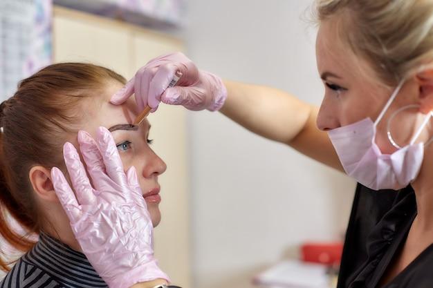 Profesjonalna kosmetyczka robi ślad na twarzy klienta przed tatuażem brwi, trwałym makijażem.