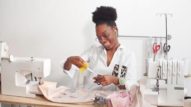 Profesjonalna krawiecka afroamerykańska kobieta projektuje ubrania w warsztacie projektanta