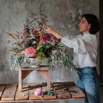 Profesjonalna kwiaciarnia przygotowuje aranżację dzikich kwiatów.