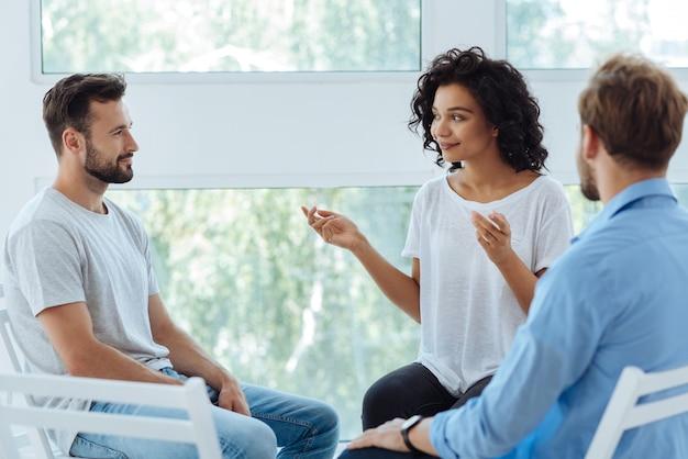Profesjonalna miła pozytywna terapeutka przyglądająca się swoim pacjentom i uśmiechnięta, gotowa do rozpoczęcia sesji psychologicznej