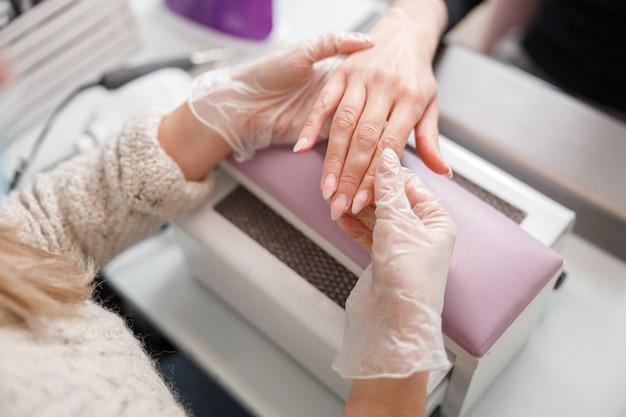 Profesjonalna mistrzyni manicure robi paznokcie dla klientki w gabinecie kosmetycznym