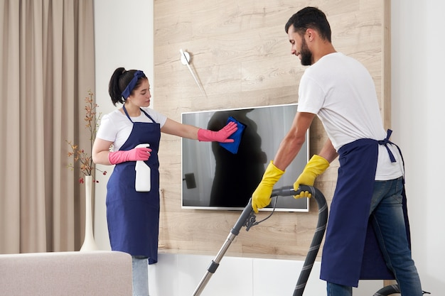 Profesjonalna obsługa sprzątająca sprząta pokój dzienny w nowoczesnym mieszkaniu