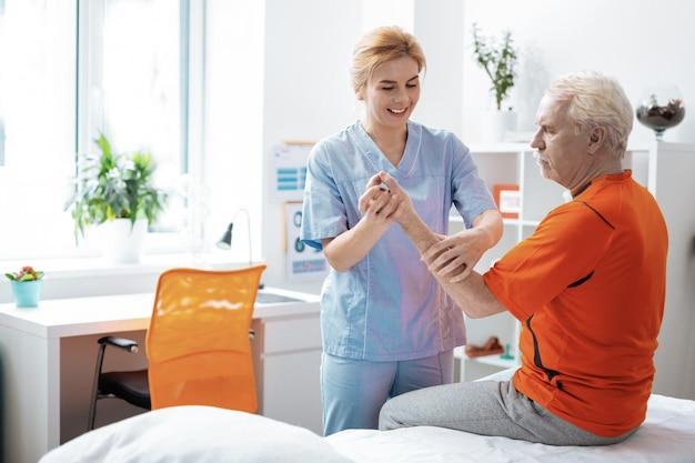Profesjonalna pielęgniarka. radosna, pozytywna kobieta uśmiechająca się podczas masowania dłoni pacjenta