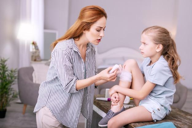 Profesjonalna pielęgniarka. wykwalifikowana miła kobieta trzymająca bandaż podczas udzielania pierwszej pomocy młodej dziewczynie