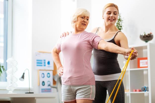Profesjonalna pomoc. miła trenerka stojąca za pacjentką, pomagając jej wykonać ćwiczenie