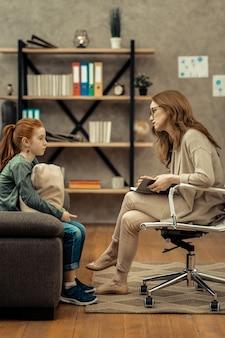 Profesjonalna pomoc. profesjonalna kobieta psycholog trzymająca notatnik podczas słuchania swojego małego pacjenta