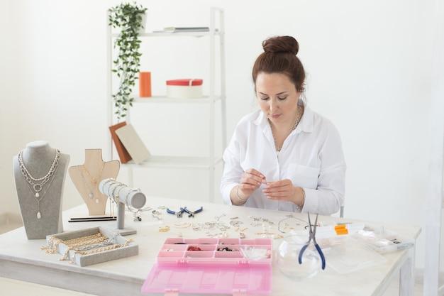Profesjonalna projektantka akcesoriów wykonująca ręcznie robioną biżuterię w pracowni mody warsztatowej