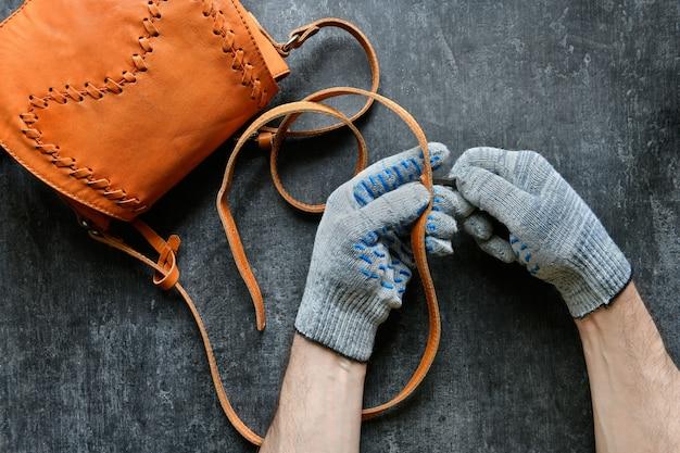 Profesjonalna skóra robi dziurę w skórzanym pasku na ramię damskiej torebki