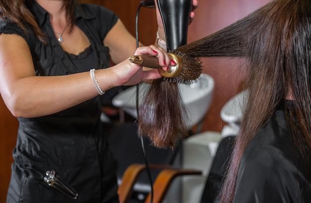 Profesjonalna stylistka suszy włosy suszarką klienta w studio fryzjerskim