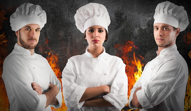 Profesjonalna szefowa kuchni kobieta i mężczyźni z pewnymi siebie minami z płomieniami ognia