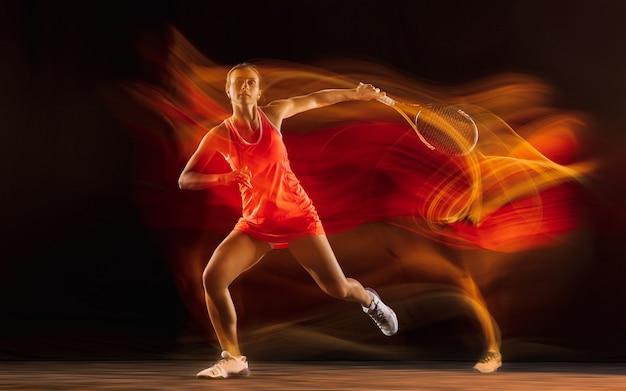 Profesjonalna tenisistka na białym tle na czarnym tle studia w mieszanym świetle
