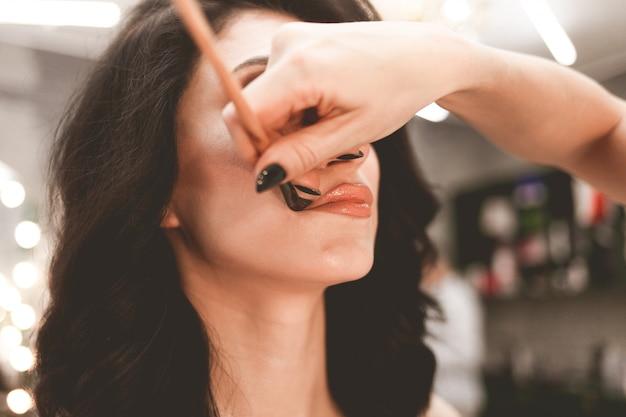 Profesjonalna visagiste robi makijaż pięknej kobiecie. ręka artysty makijażu za pomocą pędzla nakłada proszek na usta