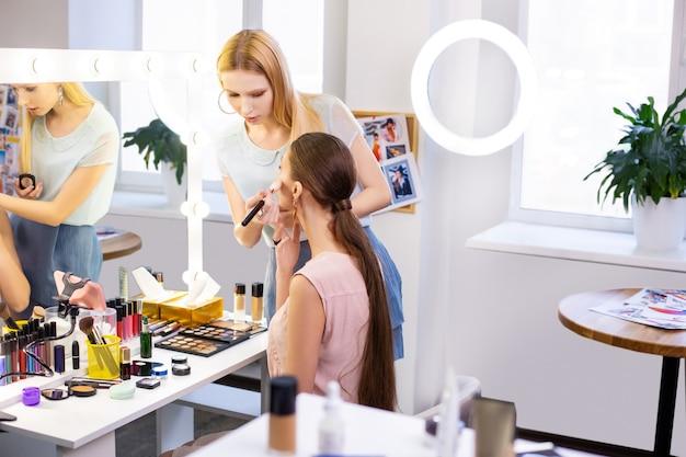 Profesjonalna wizażystka patrząca na twarz swoich klientów podczas nakładania makijażu