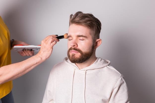 Profesjonalna wizażystka robi makijaż młodego człowieka w studio