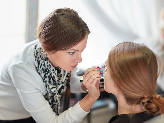 Profesjonalna wizażystka wykonuje makijaż w salonie kosmetycznym.