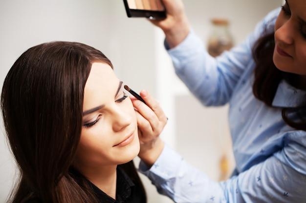 Profesjonalna wizażystka wykonuje makijaż wieczorowy dla młodej kobiety.