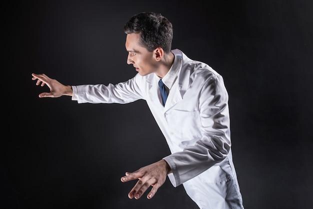 Profesjonalne badania naukowe. przyjemny przystojny, inteligentny mężczyzna ubrany w fartuch laboratoryjny i stojący przed dwoma monitorami cyfrowymi podczas pracy w laboratorium