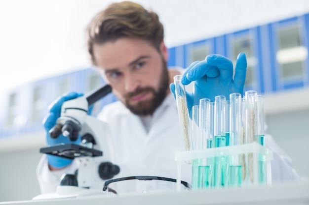 Profesjonalne badania. selektywne ogniskowanie probówki z próbką pobraną przez przystojnego naukowca podczas prowadzenia badań