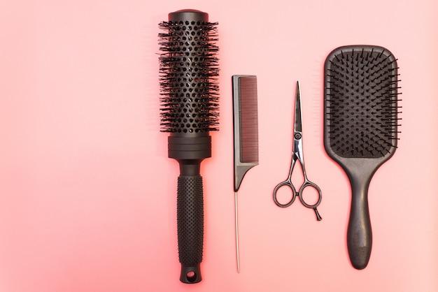 Profesjonalne czarne grzebienie i nożyczki. narzędzia fryzjerskie na różowym pastelowym tle. różne szczotki do włosów do różnych celów