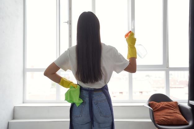 Profesjonalne mycie okien. widok z tyłu młodej kobiety, sprzątaczki w żółtych gumowych rękawiczkach, trzymając szmatę i spray podczas czyszczenia dużego okna w domu. koncepcja usług sprzątania i sprzątania