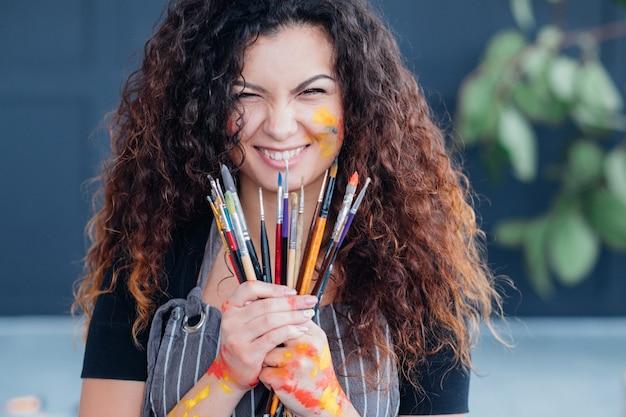 Profesjonalne narzędzia artystyczne. portret damy brunetka z kręconymi włosami, trzymając zestaw pędzli.