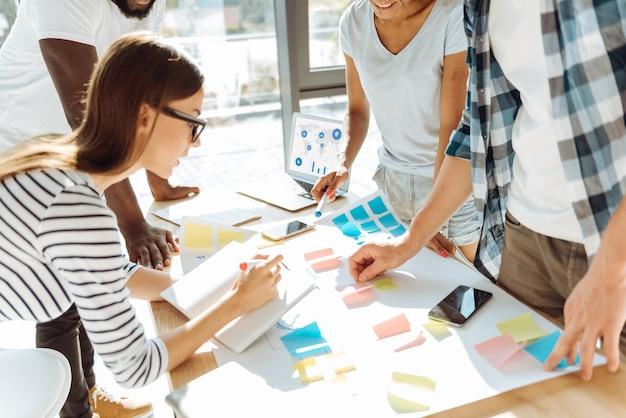 Profesjonalne podejście. młodzi entuzjastyczni ludzie stoją w biurze i omawiają swoje pomysły podczas pracy nad projektem