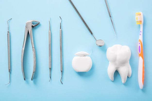 Profesjonalne stalowe instrumenty dentystyczne z lustrem w pobliżu modelu białego zęba, szczoteczką do zębów i nicią dentystyczną na jasnoniebieskim stole.