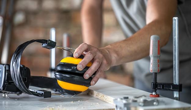 Profesjonalne stanowisko pracy stolarza ze słuchawkami ochronnymi, ochrona osobista do pracy w warsztacie produkcji stolarki.