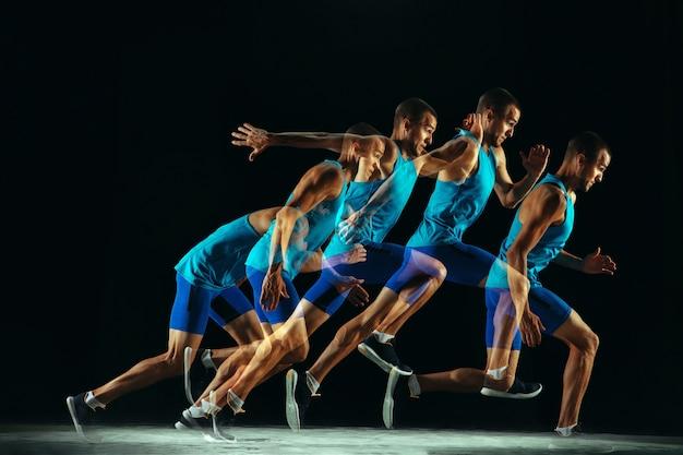 Profesjonalne szkolenie męskie biegacz na białym tle na czarnym tle studio w mieszanym świetle. mężczyzna w stroju sportowym ćwiczy w biegu lub joggingu. koncepcja zdrowego stylu życia, sportu, treningu, ruchu i akcji.