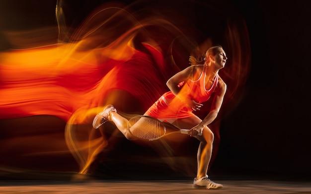Profesjonalne tenisistka szkolenia na białym tle na tle czarnego studia w mieszanym świetle. kobieta w strój sportowy.
