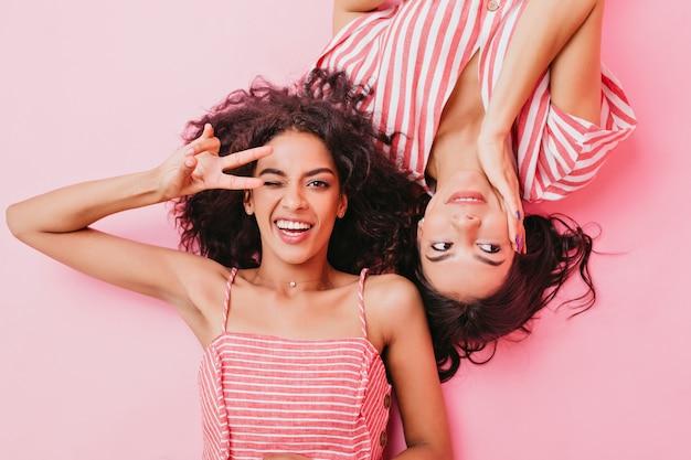 Profesjonalne zdjęcie młodych i atrakcyjnych dziewczyn z pięknym makijażem i ciemnymi kręconymi włosami. kobiety leżą na podłodze, wygłupiając się i pokazując znak pokoju.