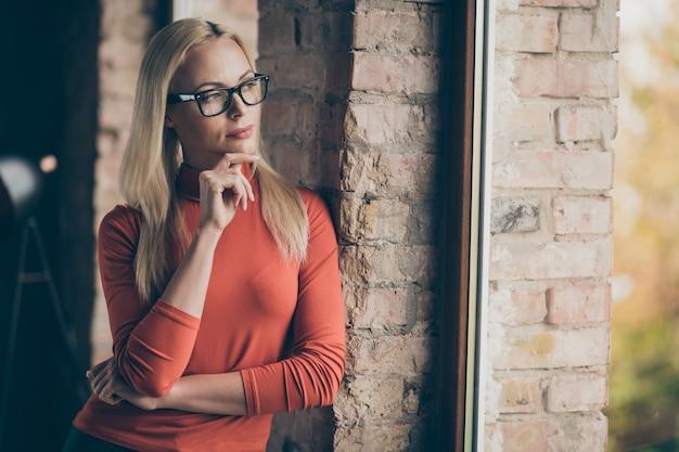 Profesjonalne zdjęcie z boku zamyślonej przedsiębiorcy, uroczej kobiety stojącej przy oknie, myśl o wyborze start-upu, zdecyduj się na decyzję, noś czerwony golf na poddaszu biurowym