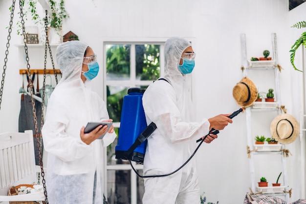 Profesjonalne zespoły do dezynfekcji pracownika w masce ochronnej i białym kombinezonie dezynfekującym w sprayu czyszczącym