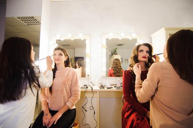 Profesjonalni charakteryzatorzy pracujący z pięknymi młodymi kobietami.