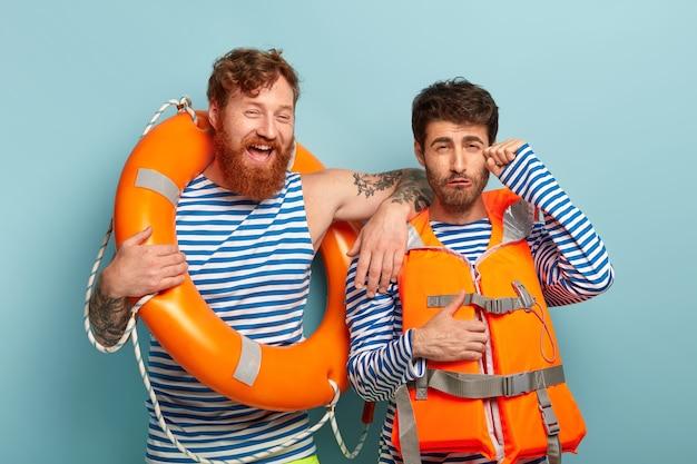 Profesjonalni faceci pozujący na plaży z kamizelką ratunkową i kołem ratunkowym