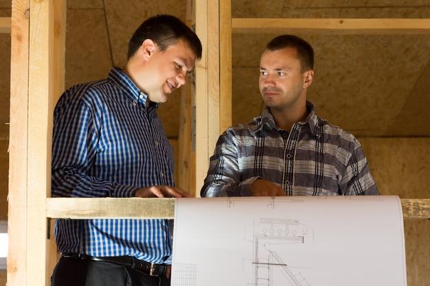 Profesjonalni projektanci płci męskiej w średnim wieku rozmawiają o projektach budowlanych na budowie.