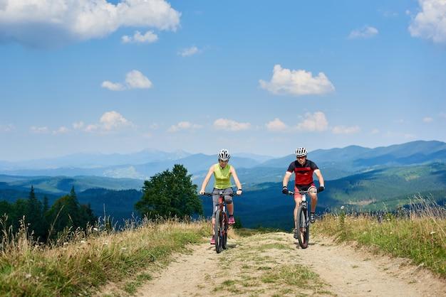 Profesjonalni rowerzyści para rowerzystów na rowerze na szlaku
