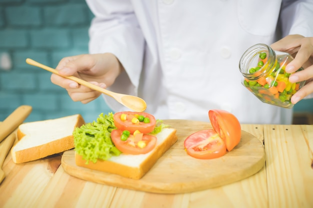 Profesjonalni szefowie kuchni z gwiazdką przewodnika michelin przygotowują i przygotowują śniadania w kuchni, dbając, aby jedzenie było smaczne i piękne.