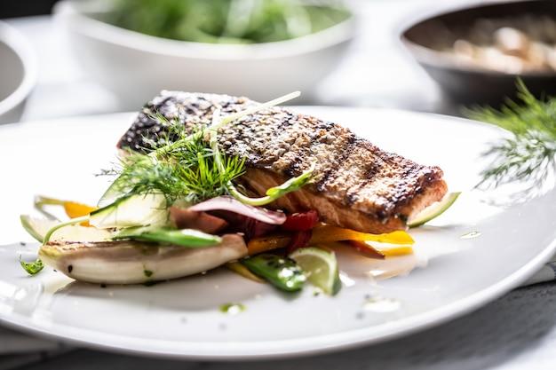 Profesjonalnie podana grillowana ryba ze skórą podana na grillowanych warzywach z limonką.