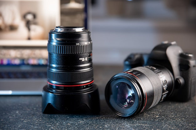 Profesjonalny aparat i obiektyw zbliżenie na pulpicie fotografa na rozmytym tle.