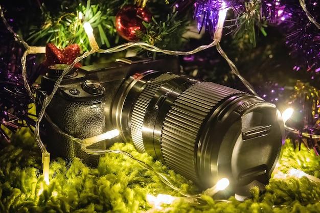 Profesjonalny aparat jako prezent na nowy rok lub boże narodzenie. ten aparat nie ładuje się pod choinką w jasnym świetle.