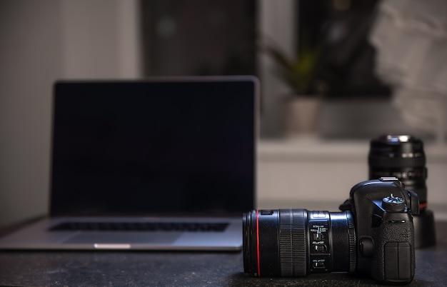 Profesjonalny aparat na niewyraźne tło z laptopem. koncepcja pracy ze zdjęciami i filmami.