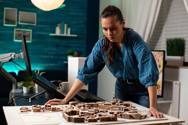 Profesjonalny architekt stojący przy stole makiety