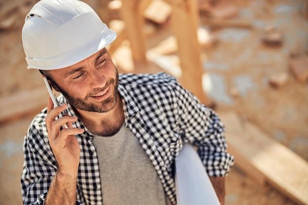 Profesjonalny architekt wykonujący telefon i trzymający rolkę papieru