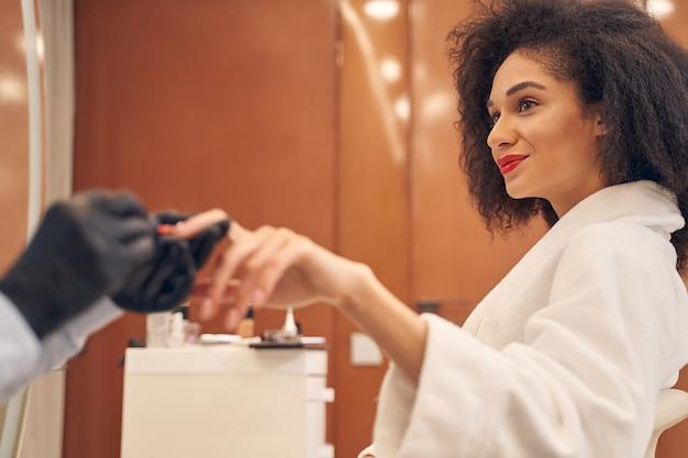 Profesjonalny artysta manicure w czarnych rękawiczkach i polerujący paznokcie klienta