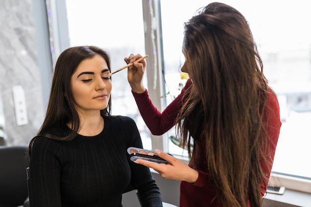 Profesjonalny artysta nakłada puder do makijażu na modelowe powieki