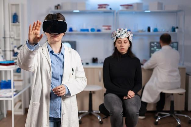 Profesjonalny badacz noszący okulary wirtualnej rzeczywistości, wykorzystujący innowacje medyczne w laboratorium analizującym skan mózgu pacjenta. zespół lekarzy neurologów pracujących na sprzęcie high-tech symulatora.