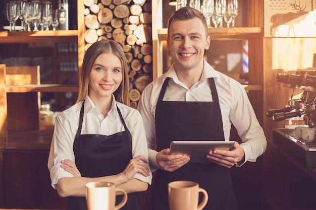 Profesjonalny barista. młoda kobieta i mężczyzna w fartuchach patrząc na kamery, uśmiechając się i stojąc przy barze. używają tabletu
