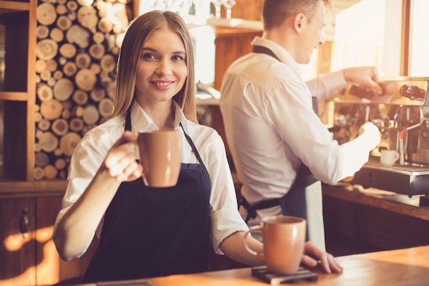 Profesjonalny barista. młoda kobieta i mężczyzna w fartuchach pracujących na ladzie barowej. kobieta trzyma filiżankę kawy